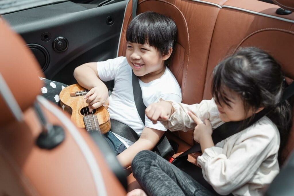 two children are enjoying company in a car seat